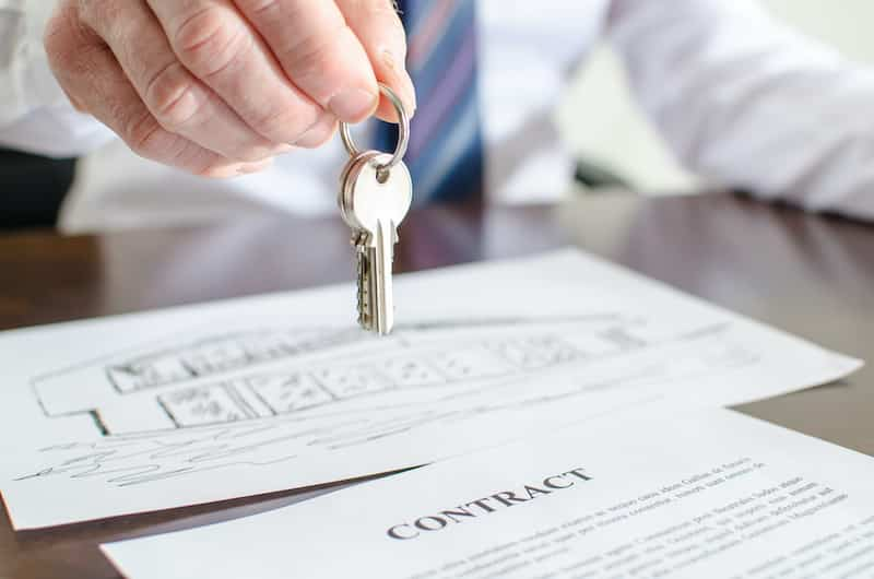 male hand holding house keys over a contract