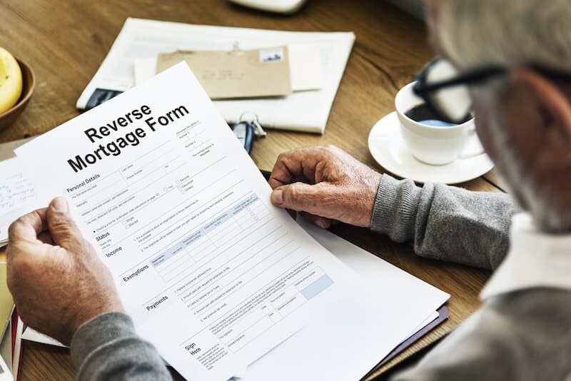 Man Holding Reverse Mortgage Form on table
