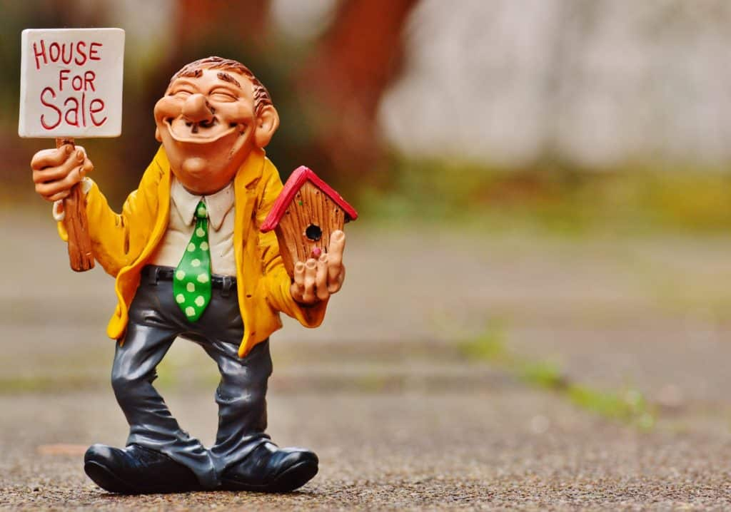 figurine holding a house for sale sign