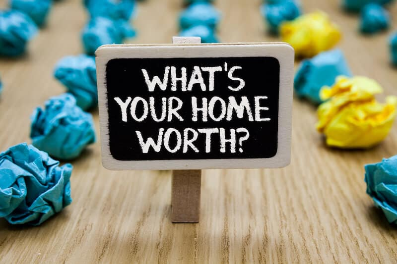 sign saying whats your home worth with crumpled papers around