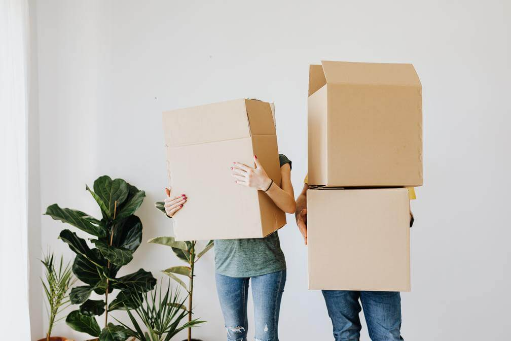 people moving holding boxes