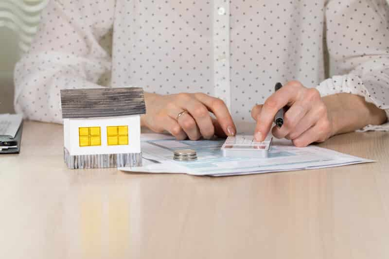 woman computing closing costs for selling a house in New York